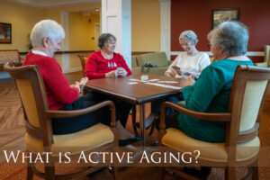 Four women demonstrating active aging by sitting sitting at a card table playing cards.