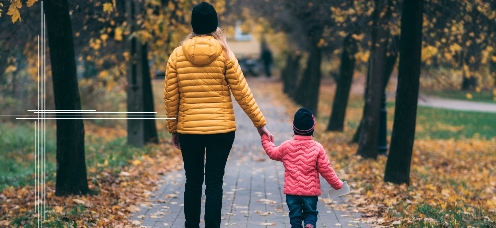 A parent and a child taking a walk during the fall amongst the foliage